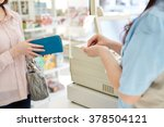young female cashier helping a... | Shutterstock . vector #378504121