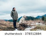 Stock photo man and labrador dog walking in mountains 378512884
