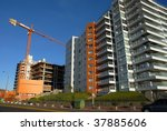 Construction crane and buildings in a city street. Wide Angle. Blue sky background - stock photo