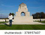 "Small photo of Arras, France - November 11, 2014: A visitor to the Cabaret Rouge World War One cemetery inspects the wreath laid at the monument to the fallen near the entrance - ""Their name liveth for ever more."""