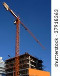 Crane at a building construction. Blue sky background - stock photo