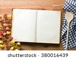 cookbook and heart shaped pasta on wooden table - stock photo