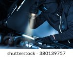 Under Hood Car Alarm Disabling by Thief. Car Thief Concept. Thief with Flashlight. - stock photo