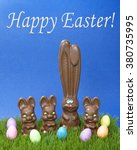 Small photo of Tall chocolate bunny with three short child sized bunnies on grass with easter eggs blue textured background. Happy Easter text in white above