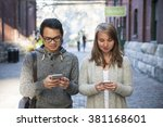 Stock photo two young people looking into smartphones while walking on city street 381168601