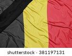 waving national flag of belgium with black mourning ribbon