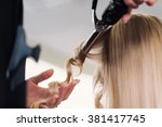 Curling Woman's Hair Giving A...
