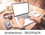 man using the labtop on a desk... | Shutterstock . vector #381593629