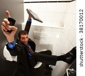 businessman sitting on toilet with hands up - stock photo