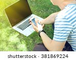 young man with laptop outdoors | Shutterstock . vector #381869224
