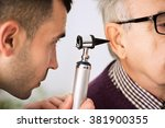 doctor examining ear of a old... | Shutterstock . vector #381900355