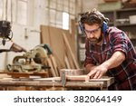 skilled carpenter cutting a... | Shutterstock . vector #382064149