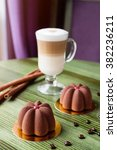Small photo of Mini mousse cakes covered with chocolate velour with glass of latte on green table in cafe. Modern european cake with coffee flavor. Shallow focus