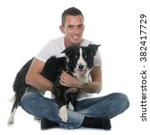 Stock photo man and border collie in front of white background 382417729