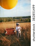 Small photo of little boy traveler standing next to a aerostat in field
