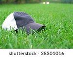 Gray Baseball Cap On A Green...