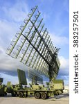 Small photo of Air defense radars and locators of military mobile antiaircraft systems in green color, modern army industry, beautiful clouds and blue sky on background