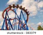 This is a shot of a modern steel roller coaster in action. - stock photo