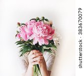 Stock photo girl with pink peonies bouquet at white wall 383670079