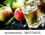 Cold apple juice with crushed ice, fresh apples with green leaves on a dark background, selective focus