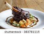 Small photo of Glazed roast lamb shank on bed of chopped vegetables. On wood surface.