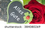 Small photo of red rose and a stone with heart sign and the german words all the best / All the best