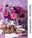 cup of tea and a bouquet of flowers in a white jug - stock photo