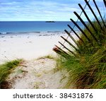 Dunes, grass and fence and an empty beach - stock photo