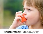 Small photo of Portrait of a girl using asthma inhaler outdoors
