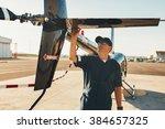male pilot in uniform examining ... | Shutterstock . vector #384657325