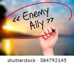 Small photo of Man Hand writing Enemy - Ally with black marker on visual screen. Isolated on background. Business, technology, internet concept. Stock Photo