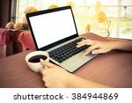 laptop and hand holding coffee... | Shutterstock . vector #384944869