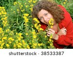 Young Woman Smelling Yellow...
