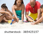 Small photo of Family making sandcastles