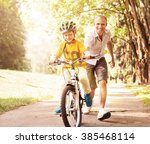 first lessons bicycle riding | Shutterstock . vector #385468114