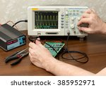 Small photo of Workplace engineer. Man's hand adjusts the amplitude of the sine wave on an oscilloscope.