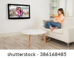 young woman sitting on sofa... | Shutterstock . vector #386168485