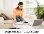 young woman sitting on sofa... | Shutterstock . vector #386168884