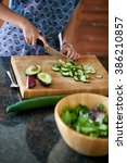 mature woman chopping vegetables | Shutterstock . vector #386210857