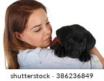 Stock photo  picture of a woman with her black labrador puppy 386236849
