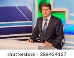 male anchorman in tv studio.... | Shutterstock . vector #386424127