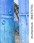 Small photo of Blue doors ajar allowing view of courtyard in Morocco