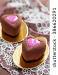 Small photo of Heart shaped mini mousse cakes covered with chocolate velour and decorated with pink glaze on brown lace background. Modern european cake for valentines. Shallow focus