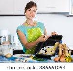 happy woman preparing merluccid ... | Shutterstock . vector #386661094