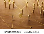 Small photo of Linking entities. Dispute or conflict, or Bottleneck between two entities. Network, networking, social media, internet communication abstract. Web of gold wires on rustic wood.