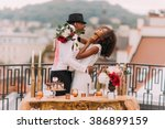 Small photo of Stylish african wedding couple having fun on the balcony with luxury golden table in oriental style on foreground