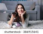 young beautiful woman watching... | Shutterstock . vector #386915641