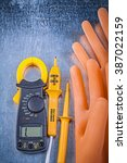 Small photo of Digital ammeter electric tester electricians rubber gloves on metallic background electricity concept.