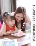 family eating cake in restaurant | Shutterstock . vector #387103441