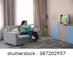 young couple watching tv on a...   Shutterstock . vector #387202957